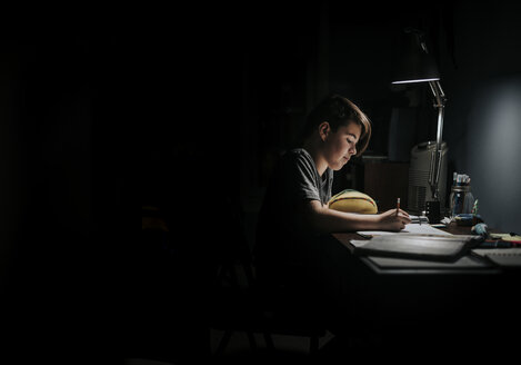 Side view of boy studying at table in darkroom - CAVF51988