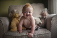 Portrait of cute shirtless baby boy on armchair at home - CAVF52030