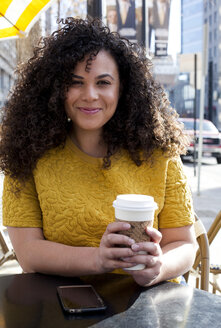 Portrait of smiling woman holding disposable cup while sitting at sidewalk cafe in city - CAVF52078