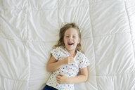 Overhead portrait of cheerful girl lying on bed - CAVF52081