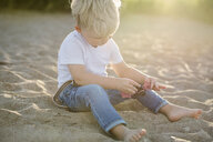 Baby boy playing with toy while sitting on sand at beach - CAVF52099