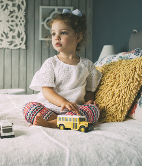 Thoughtful girl with toys sitting on bed - CAVF52144