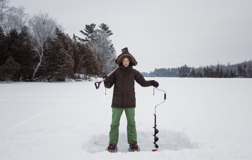 Portrait of man holding ice auger and shovel while standing on frozen lake against sky - CAVF52153