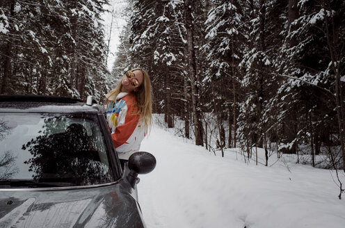 Playful woman blowing bubble gum while sitting on car's window during winter - CAVF52159