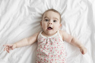 High angle portrait of baby girl lying on bed at home - CAVF52162