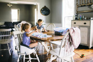 Sister painting while brother sitting on dining table at home - CAVF52174