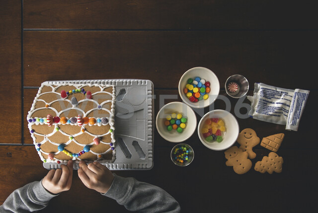Cropped hands of boy making gingerbread house on wooden table during Christmas at home - CAVF52231