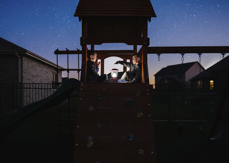 Brothers with illuminated lantern sitting on outdoor play equipment against star field at park - CAVF52267