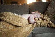 Baby boy lying on sofa at home - CAVF52288