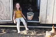 Full length of girl sitting in animal pen - CAVF52300