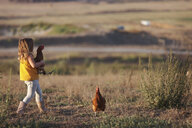 Side view of girl holding hen while walking on field - CAVF52303