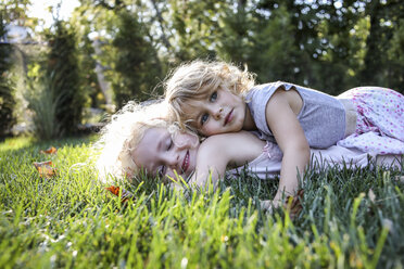 Sisters lying on grassy field at park - CAVF52339