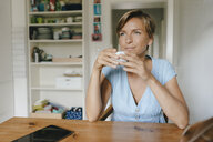 Woman sitting at table at home with cup of coffee - KNSF05038