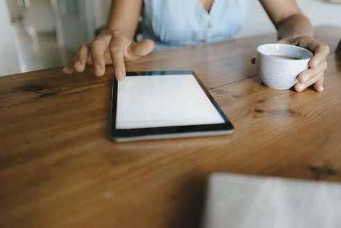Close-up of woman sitting at table at home with cup of coffee and tablet - KNSF05050