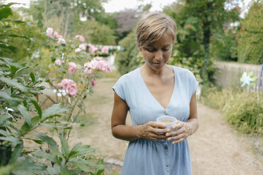 Woman standing in garden with cup of coffee - KNSF05053