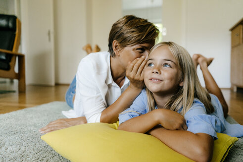 Mother and daughter lying on the floor at home whispering - KNSF05056