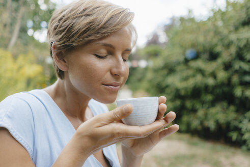 Portrait of woman with closed eyes in garden holding cup of coffee - KNSF05059