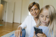 Mother and daughter looking at smartphone together - KNSF05065