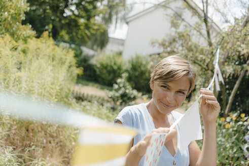 Portrait of smiling woman hanging up pennants in garden - KNSF05071