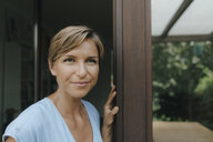 Portrait of confident woman at French window - KNSF05074