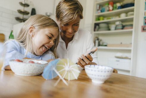Happy mother and daughter having fun at table at home - KNSF05083