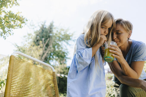 Mother and daughter sharing a smoothie in garden - KNSF05089