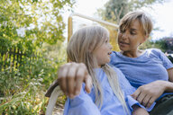 Mother and daughter relaxing in garden - KNSF05095