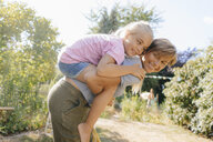 Happy mother carrying daughter piggyback in garden - KNSF05098