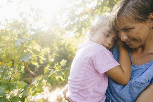 Happy mother carrying daughter in garden - KNSF05104
