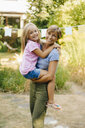 Happy mother carrying daughter in garden - KNSF05110