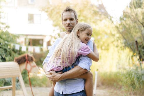 Portrait of father carrying daughter in garden - KNSF05128
