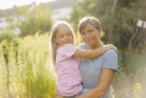 Portrait of smiling mother carrying daughter in nature - KNSF05131