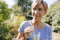 Portrait of woman drinking a soft drink in garden - KNSF05137