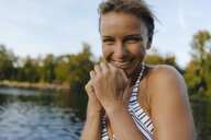 Portrait of happy woman wearing a bikini at a lake - KNSF05143