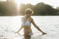 Portrait of woman wearing a bikini in a lake - KNSF05155