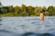 Portrait of smiling woman swimming in a lake - KNSF05161