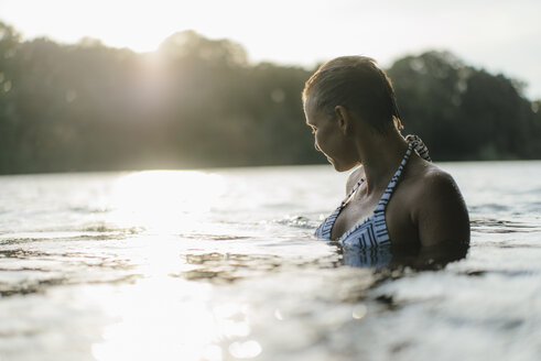 Woman in a lake at sunset - KNSF05167