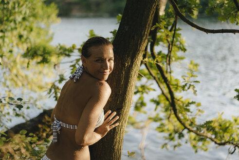Portrait of smiling woman wearing a bikini at tree trunk at a lake - KNSF05170