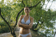 Portrait of smiling woman wearing a bikini at a lake - KNSF05176