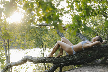 Relaxed woman wearing a bikini lying on a tree trunk at a lake - KNSF05179