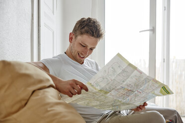 Smiling young man sitting on couch at home reading map - RHF02197