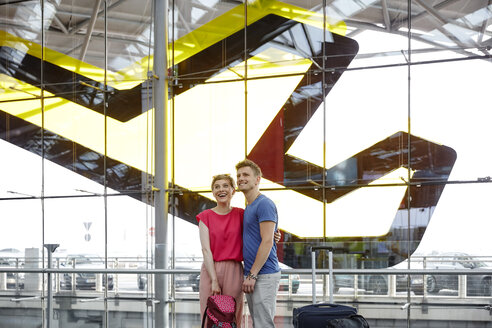 Happy couple standing at the airport - RHF02215