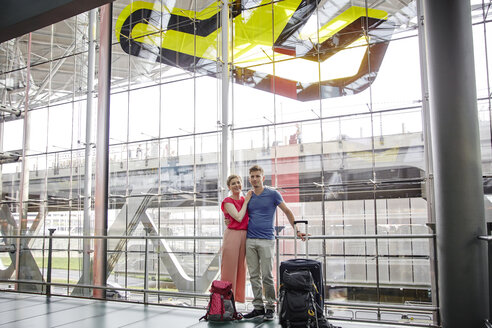 Smiling couple standing at the airport - RHF02218