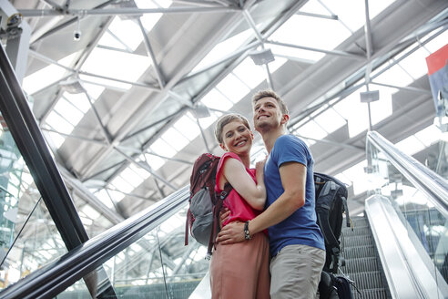 Happy couple on escalator at the airport - RHF02221