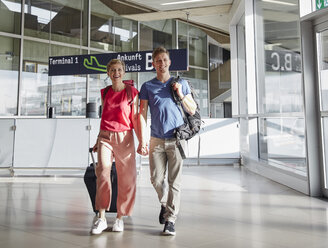 Happy couple walking hand in hand at the airport - RHF02245