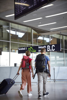 Rear view of couple walking at the airport - RHF02251