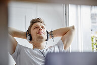 Relaxed young man at home listening to music with headphones - RHF02260