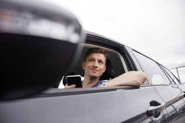 Smiling young man with cell phone in a car - RHF02263