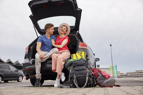 Happy young couple sitting in car boot at the airport - RHF02272