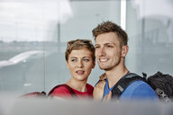 Portrait of smiling couple at the airport looking out of window - RHF02278
